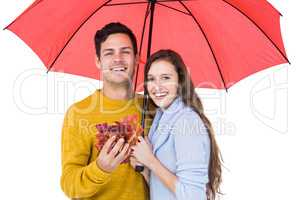 Happy couple under an umbrella holding leaves