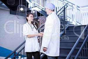 Doctors shaking hands on staircase