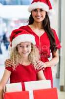 Mother and daughter in Christmas attire standing with Christmas