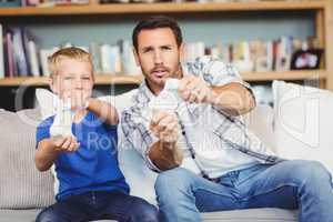 Smiling father and son playing video game while sitting on sofa