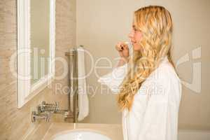 Blonde woman about to brush her teeth