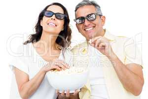 Smiling couple with 3D glasses eating popcorn