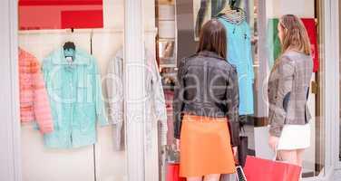 Two rear women window shopping in mall