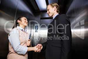 Businessman shaking hands with businesswoman in elevator