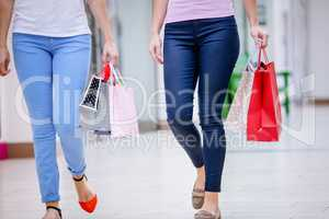 Women walking in mall with shopping bags