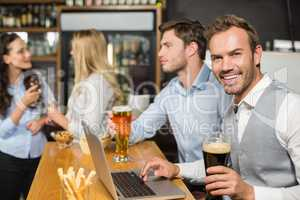 Men working on laptop while women talk behind
