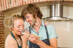 Handsome man making his girlfriend taste the preparation