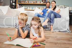 Children coloring on book while parents looking at them
