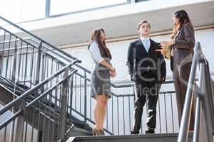 Three executives standing on a staircase