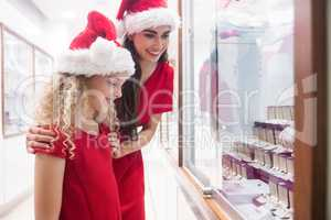 Mother and daughter in Christmas attire looking at jewelry displ
