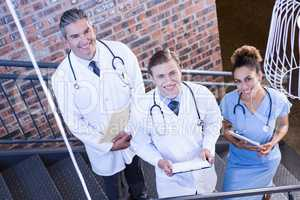 Portrait of doctors standing on staircase with document