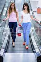 Two beautiful women on escalator of shopping mall