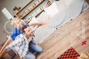 Tilt image of father and son playing on floor