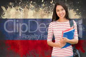 Composite image of college girl holding books with blurred stude