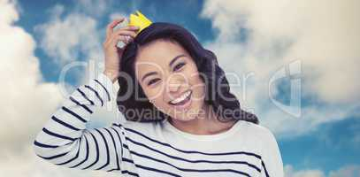 Composite image of smiling asian woman with paper crown