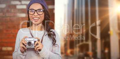 Composite image of asian woman holding digital camera