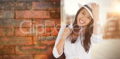 Composite image of woman with casual clothes holding her hat