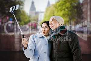 Composite image of playful couple taking selfie against building