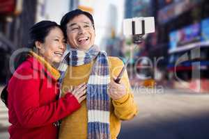 Composite image of older asian couple on balcony taking selfie