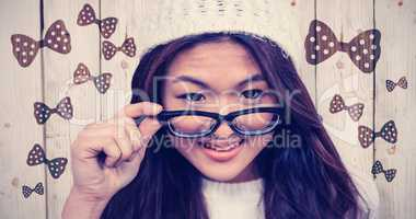 Composite image of smiling asian woman holding eyeglasses
