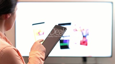 Woman watches television while holding a tablet device