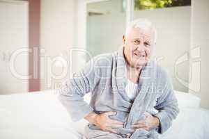 Portrait of senior man frowning with stomach ache