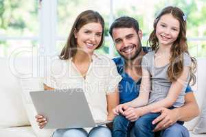 Portrait of family with laptop sitting on sofa