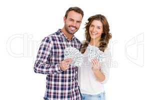 Happy young couple holding fanned out currency notes