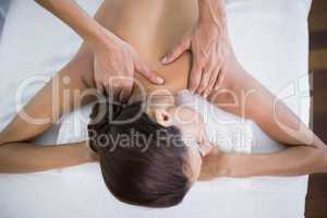 Woman receiving back massage at health spa