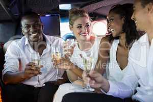 Well dressed people drinking champagne in a limousine