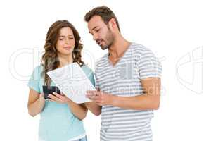 Worried couple calculating bill on calculator