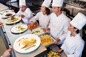 Chefs standing at serving trays of pasta