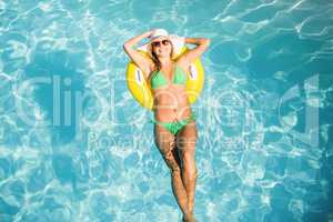 Happy woman in green bikini floating on inflatable tube in swimm