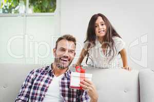 Happy daughter and father with gift at home