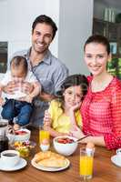 Portrait of smiling family at breakfast table