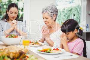Mother and daughter with granny praying at dining table