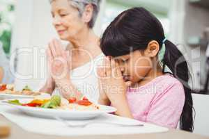 Granny and granddaughter praying at dining table