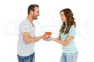 Happy young couple holding model house