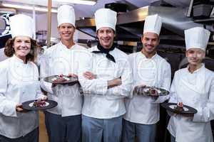 Happy chefs presenting their dessert plates