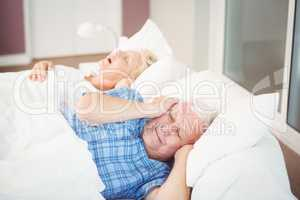 Disturbed man covering ears from snoring wife