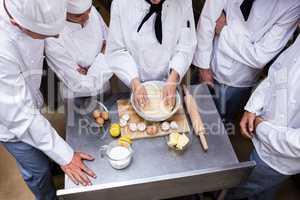 Head chef teaching his team to prepare a dough