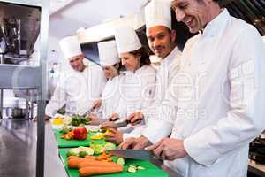 Team of chefs chopping vegetables