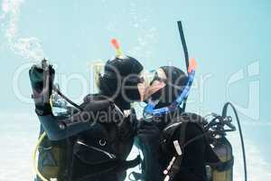 Couple kissing underwater while scuba diving