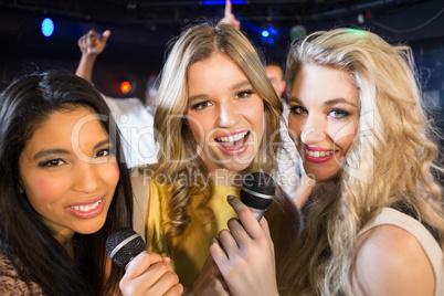 Happy friends singing at the karaoke