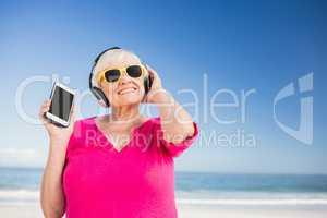 Senior woman listening music with headphone
