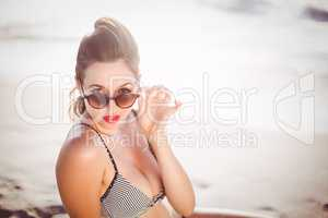 Glamorous woman looking over sunglasses on the beach