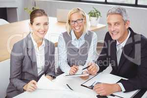 Business people smiling while sitting with client