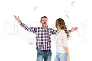 Happy young couple throwing currency notes in air