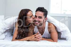 Smiling woman kissing man while lying under blanket