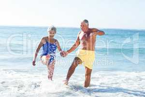Senior couple playing with waves